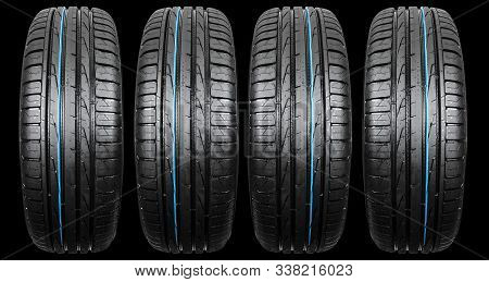 Studio Shot Of A Set Of Summer Car Tire Isolated On Black Background. Tire Stack. Car Tyre Protector
