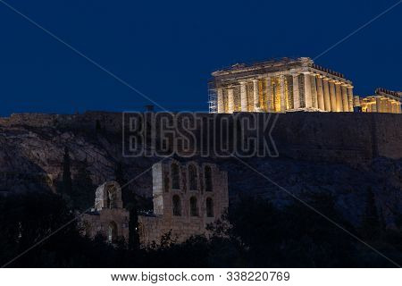 The Parthenon And Acropolis Lit Up At Night With Herodes Theater In The Foreground