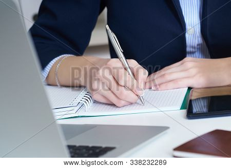 Young Businesswoman Writing In Notepad While Sitting At The Office. Female Hands Holding A Pen And M