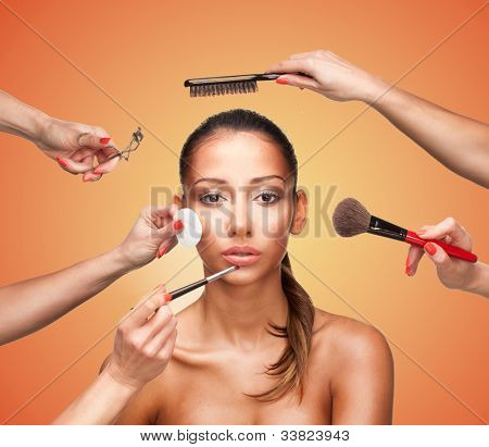 Conceptual beauty and fashion image of the hands of several beauticians and stylists holding their respective equipment giving a glamour makeover to a beautiful woman