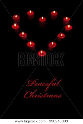 Candles burning in a shape of heart against dark background with text Peaceful Christmas; focus on bottom candle