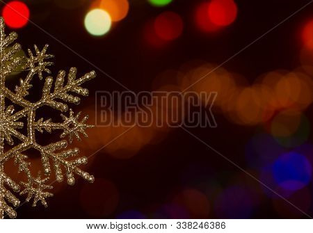 Half of a golden glittery snowflake ornament with copyspace against colorful bokeh light background