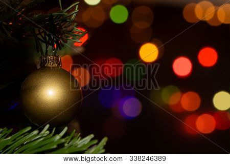 Golden bauble hanging in a Christmas tree, with bright colorful bokeh light spots on the background