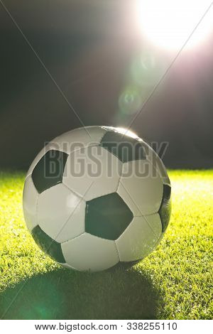 Single Soccer Ball On Green Grass Lawn Background With Lensflare From Stadium Light - Selective Focu