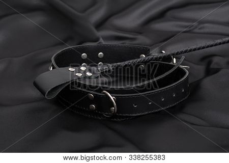 Stack For Bdsm Games And Leather Collar On Black Silk Background. Accessories For Adult Sexual Game.