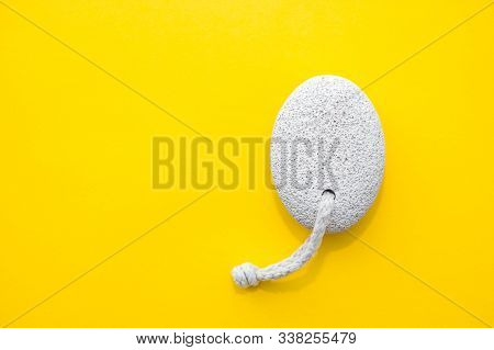 Natural Pumice Stone With White Rope On Yellow Background. Pedicure And Spa Concept. Pumice Stone Fo