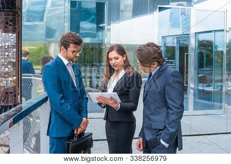Confident Businesspersons Talking In Front Of Modern Office Building. Businessmen And Businesswoman