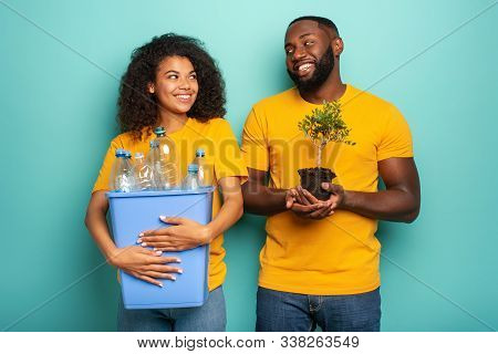 Happy Couple Hold A Plastic Container With Bottles And A Small Tree Over A Light Blue Color. Concept