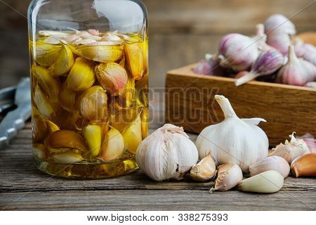 Garlic Aromatic Flavored Oil Or Infusion Bottle And Wooden Crate Of Garlic Cloves On Wooden Kitchen