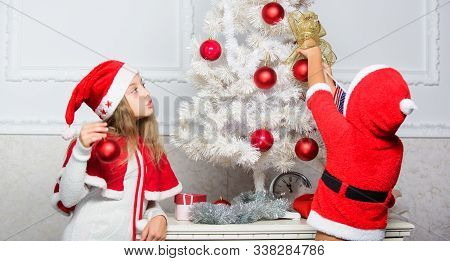 Family tradition concept. Children decorating christmas tree together. Boy and girl decorating tree. Siblings busy decorating. Cherished holiday activity. Kids in santa hats decorating christmas tree poster