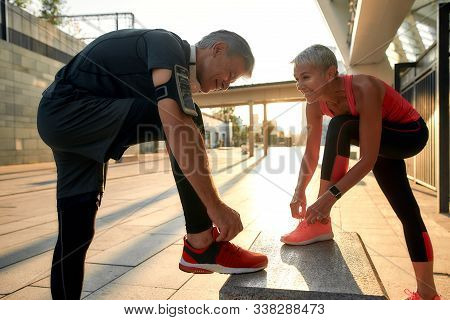 Healthy Family. Active Middle-aged Couple In Sports Clothing Tying Shoelaces Before Jogging Outdoors