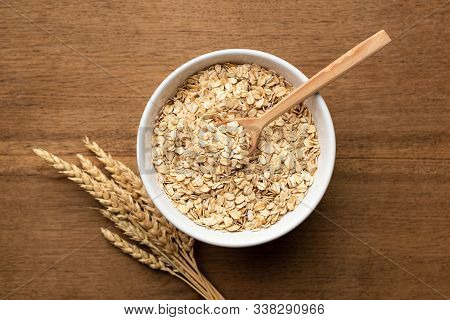 Oat Flakes, Grains, Rolled Oats In Bowl On Wooden Table Background, Top View