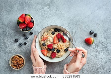 Oatmeal Porridge Bowl With Berries In Female Hands On Concrete Background. Top View, Copy Space. Hea