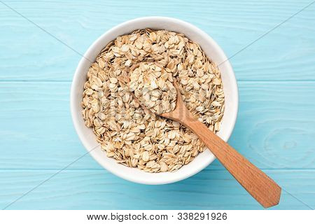 Rolled Oats, Oat Flakes In Bowl On Blue Background