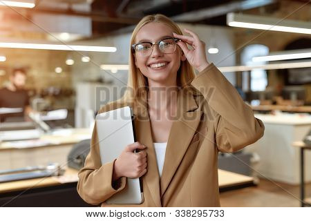 Close Up Portrait Of Young Caucasian Female Worker In Casual Wear And Glasses Smiling At Camera And