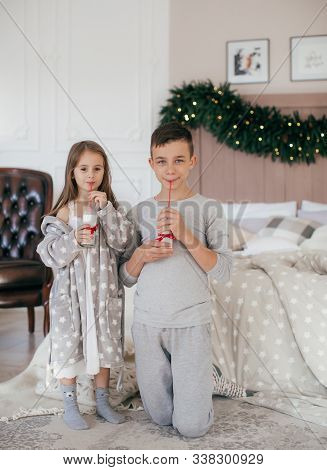 Stock Photo - Beautiful Little Girl And Boy Are On The Bed In The Bedroom With Christmas Decoration