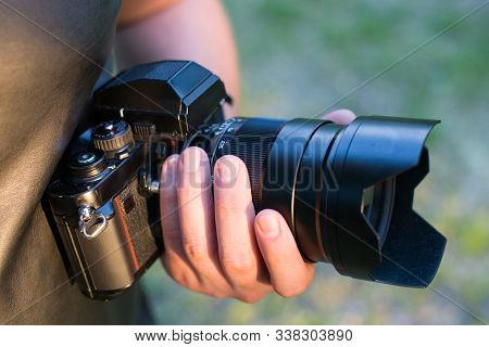 Closeup Of A Black Camera Holding By Mans Hand With Natrural Blackground In Sunny Day.