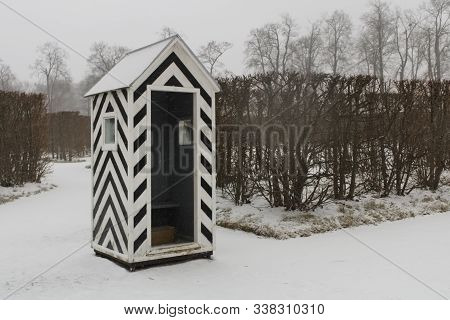 Black And White Striped Guardhouse In The Middle Of A Snowy Park