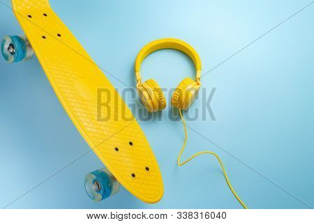 Yellow Headphones And Skateboard Or Pennyboard On Blue Background. Music Concept.