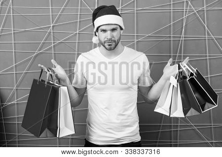 Macho Shopper In Red Hat Hold Paperbags. Xmas Sale Concept. Man Santa With Shopping Bags On Pink Bac