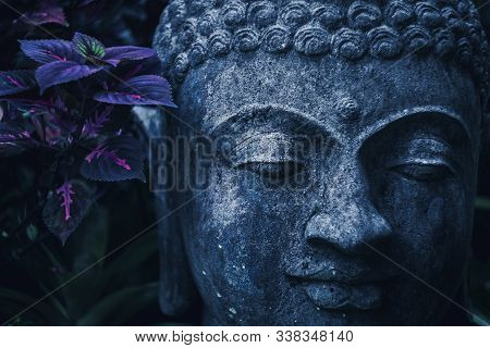 Stone Buddha Face Close-up In Trend Blue Color Toning. Handmade Carved Buddha Statue In Balinese Gar