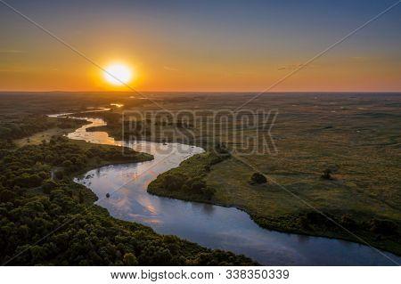 sunrise over Dismal River meandering through Nebraska Sandhills at Nebraska National Forest, aerial view of summer scenery