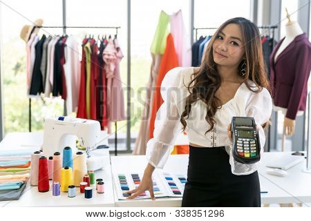 Portrait of young adult fashion designer hold EDC Machine ready for customer to make a payment with credit card at her atelier studio as sole owner. Using for entrepreneur startup consumerism concept