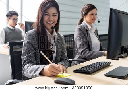 Young adult friendly and confidence operator woman agent smiling with headsets working in a call center with her colleague team working as customer service and technical support in background.
