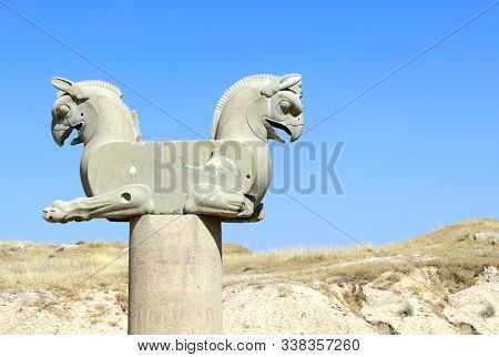 Fragment of stone column sculpture of a two-headed griffins in the ancient city of Persepolis, Iran. UNESCO World heritage site. On blue sky background