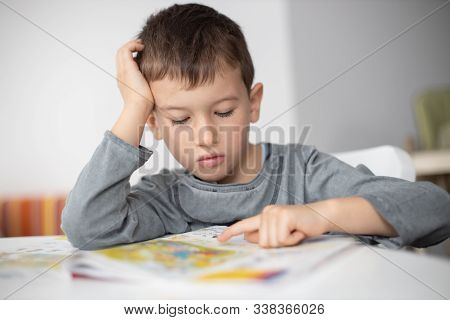 Portrait Of Young Boy Struggling With His Homework At Home. Children Education Concept