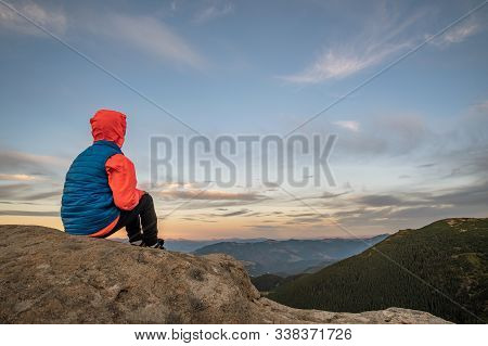 Young Child Boy Hiker Sitting In Mountains Enjoying View Of Amazing Mountain Landscape.