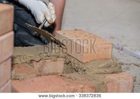 Bricklayer Builds Bricks Wall With Small Bricks - Closeup Craftsman