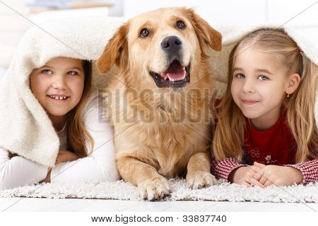 Little sisters and pet dog having fun at home, lying prone on floor, smiling under blanket.