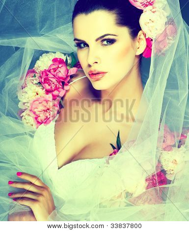 An elegant sexual brunette is in a wedding dress, decorated pink colors