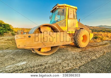 Side View Of Steamroller In A Suggestive Construction Site. Concept Of Work In Progress.