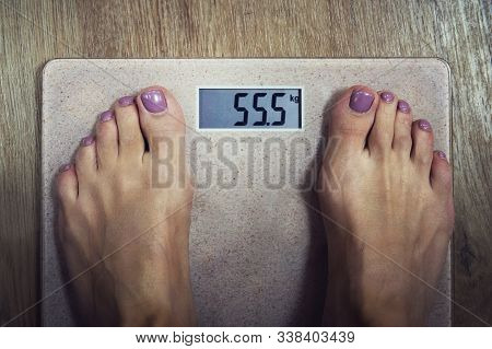 Close Up Of Digital Bathroom Scale With Female Bare Feet On It Showing 55, 5 Kilogram On Display. Wo