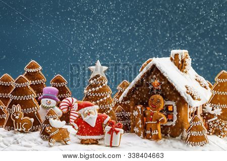 Gingerbread house christmas fir trees Santa Claus and gift cookies winter holiday celebration concept