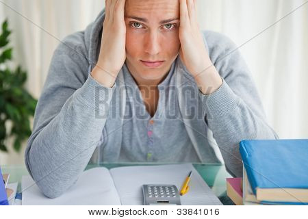 Portrait of a student holding his head while doing math in front of a calculator