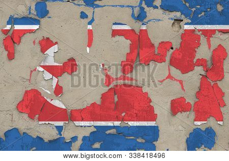 North Korea flag depicted in paint colors on old obsolete messy concrete wall closeup. Textured banner on rough background poster