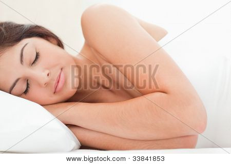 Sleeping woman resting her head on the pillow. A close up view of the woman.