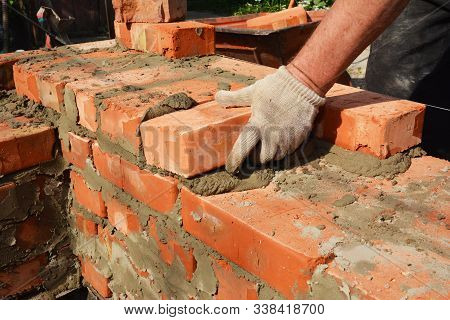 Bricklayers Hands In Masonry Gloves Bricklaying House Wall. Bricklaying,  Masonry, Brickwork Close U