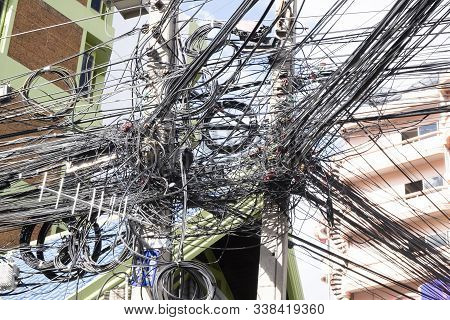 Messy Wires Attached To The Electric Mast. The Chaos Of Cables And Wires On An Electric Pole. Many E