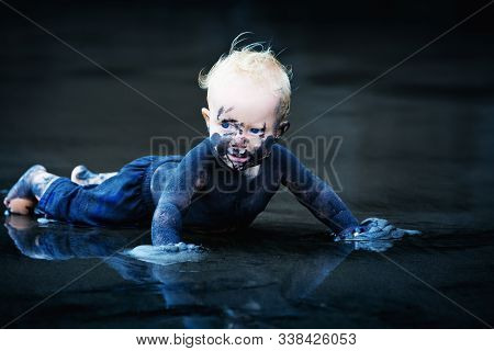 Funny Portrait Of Happy Smiling Child With Dirty Face, Hands Playing With Fun On Black Sand Beach In