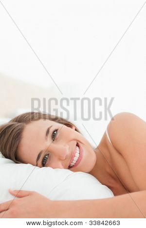 A close up shot of a woman smiling brightly in bed.