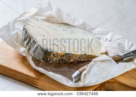 Whole Roquefort French Blue Cheese With Knife On Wooden Board.