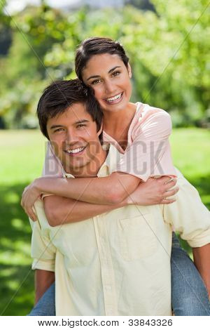 Woman smiling while looking in front of her as she is being carried bey her friend in a park