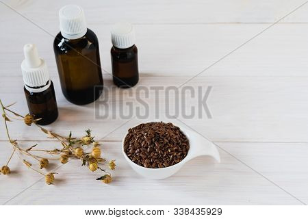 Flax Oil In Dark Glass Bottles, Flax Seeds In A Ceramic Spoon And A Sprig Of Flax