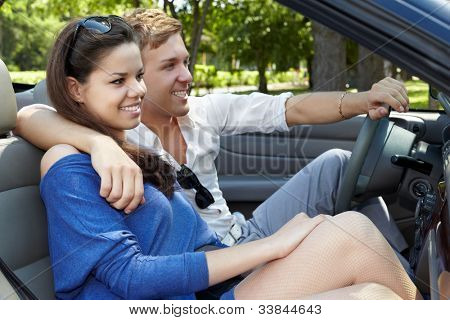 Young smiling couple sits in a cabriolet and looks forward through a windshield