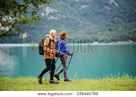 A Side View Of Senior Pensioner Couple Hiking By Lake In Nature.