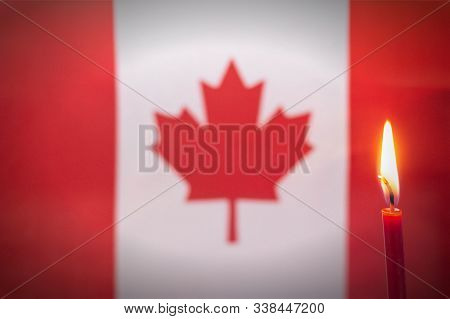 Burning Candle On The Background Of The Flag Of Canada. The Concept Of Mourning And Sorrow In The Co